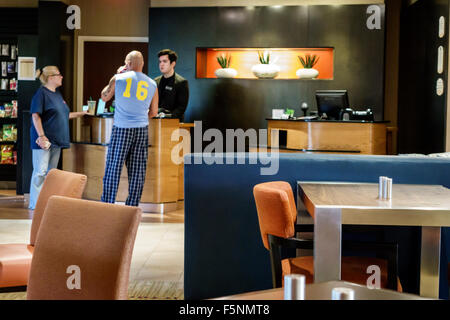 Stuart Florida Courtyard by Marriott hotel motel inside lobby front desk reservations guests couple man employee - Stock Photo