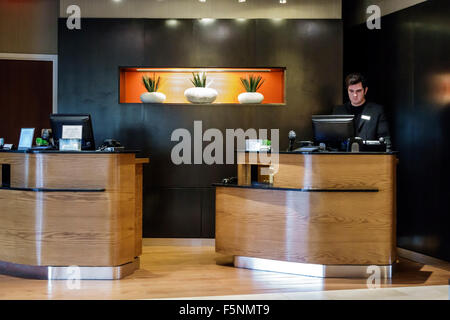 Stuart Florida Courtyard by Marriott hotel motel inside lobby front desk reservations man employee service - Stock Photo