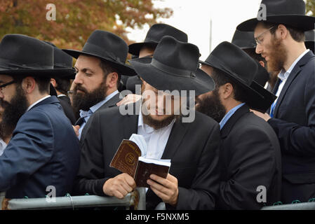 Religious Jewish men at the Ohel in Cambria Heights Queens, New York waiting to say a prayer at the Rebbe's grave. - Stock Photo