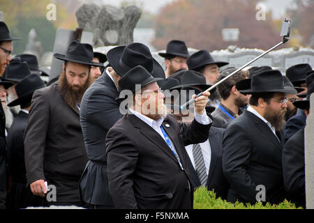 A man takes a photo of religious Jewish men at the Ohel in Cambria Heights  waiting to say a prayer at the Rebbe's - Stock Photo
