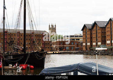 Gloucester Docks, its Victorian warehouses and wharf on a cloudy day. The Cathedral can be seen in the background - Stock Photo