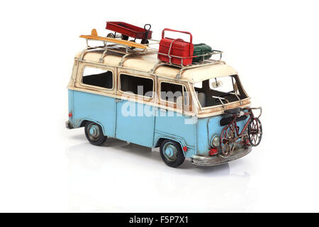Old vintage blue van toy carried beach accessory for summer holiday on white background. - Stock Photo