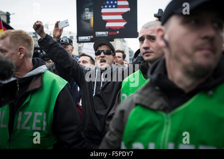 A man gestures to counter-demonstrators during a march through the streets of Berlin by the Alternative für Deutschland - Stock Photo