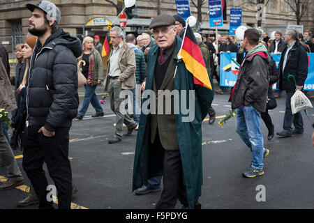 An elderly man with a German flag marching through the streets of Berlin during a demonstration by the Alternative - Stock Photo