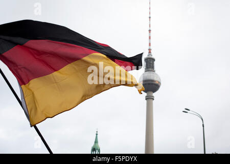 A German flag being waved aloft with the television tower in the background during a demonstration by the Alternative - Stock Photo