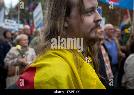 A man draped in a German flag marching during a demonstration by the Alternative für Deutschland (AfD) political - Stock Photo