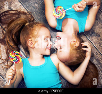Fine portrait of a twin sisters holding colorful  lollipops - Stock Photo