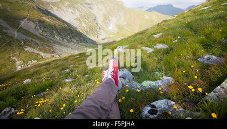 Legs of traveler sitting on a high mountain top in travel. Freedom concept - Stock Photo