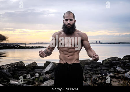 Bearded man flexes abdominal muscles at sunrise on a rocky beach. - Stock Photo