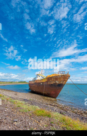 A washed up abandoned rusty boat at high tide on a summers day - Stock Photo