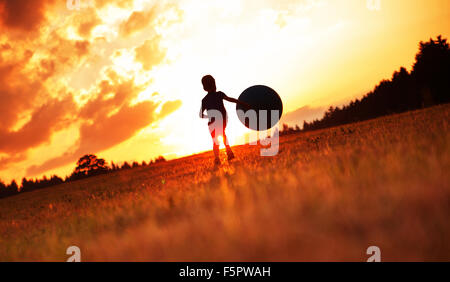Little man playing football on the meadow - Stock Photo
