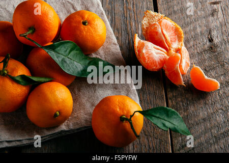 Ripe tangerines with leafs on wooden table - Stock Photo