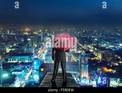 Man with red umbrella standing back on the pier against the night city - Stock Photo