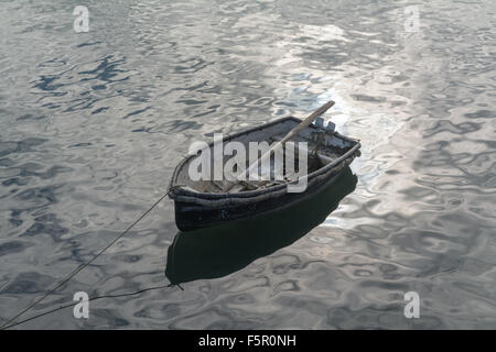 Small, old rowing boat in a harbour with bright light reflecting from surface - Stock Photo