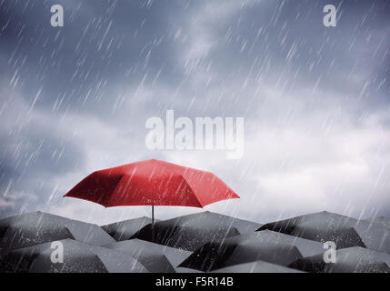 Black and one red umbrellas under rain and thunderstorm - Stock Photo