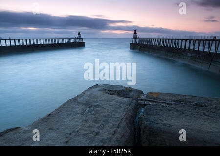 The breakwaters and pier at Whitby, North Yorkshire at sunset. - Stock Photo
