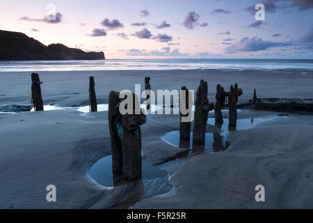 Groynes covered in barnicles on the beach at Sandsend at sunset - Stock Photo