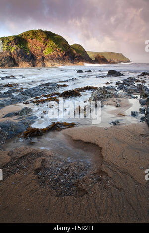 Patterns are left in the sand from tidal action and as the waves recede jagged rocks and seaweed are left on Mouthwell - Stock Photo