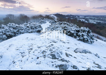 A weak sunrise is casting soft light on the snow covered path to Summer Hill, Malvern Hills, Worcestershire - Stock Photo