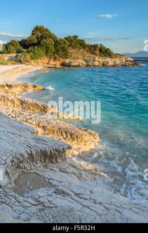 The rocks on Bataria beach, Kassiopi, Corfu are lit up with the stong orange light of sunrise. - Stock Photo