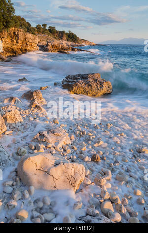 The pebbles and rocks on Bataria beach, Kassiopi, Corfu are lit up with the stong orange light of sunrise. - Stock Photo