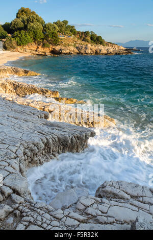 The rocks on Bataria and Kanoni beach, Kassiopi, Corfu are lit up with the stong orange light of sunrise. - Stock Photo