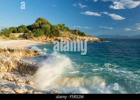 A wave crashes over the rocks on Batariaand Kanoni beach, Kassiopi, Corfu. The mountains of Albania can be seen - Stock Photo
