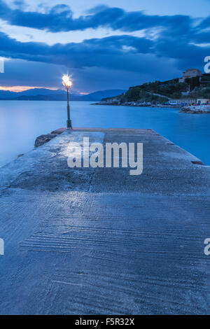 The harbour wall at Kassiopi in the morning light. A blue cast covers the water and sky. - Stock Photo