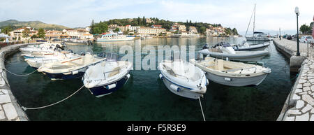 Power boats are moored up at the harbour at Kassiopi in the morning light. - Stock Photo