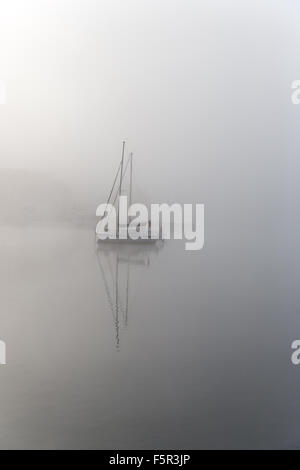 Yachts at their moorings on a misty autumn morning near Ambleside on Lake Windermere, Cumbria - Stock Photo