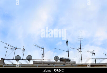 Antennas and TV satellite dish on roof against blue sky. - Stock Photo