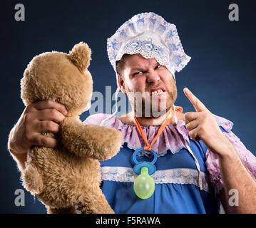 Angry man with toy bear in studio - Stock Photo