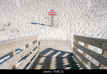 A beach sign on a Fire Island beach designating it closed to swimming. Stock Photo