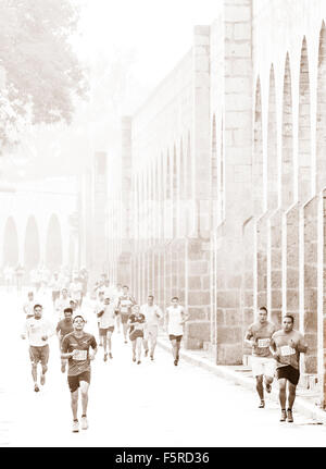 Runners compete in a 10k along the Aqueduct in Morelia, Mexico. - Stock Photo