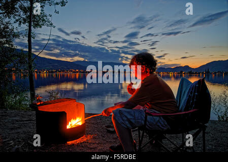 Boy roasts marshmallow in campfire at lakeshore campsite, sẁiẁs  Provincial Park, Osoyoos, British Columbia, Canada - Stock Photo