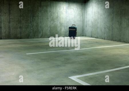 Forgotten Suitcase in Empty Parking Garage - Stock Photo