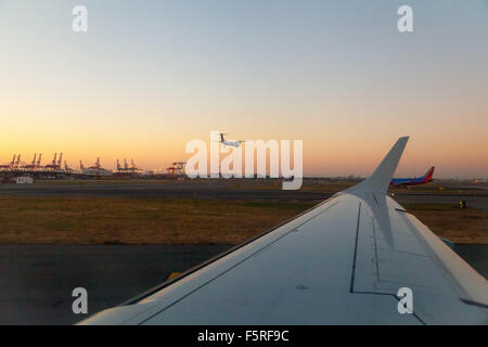 looking out the plane window across the wing of the plane to see another plane landing, during sunrise at Newark - Stock Photo