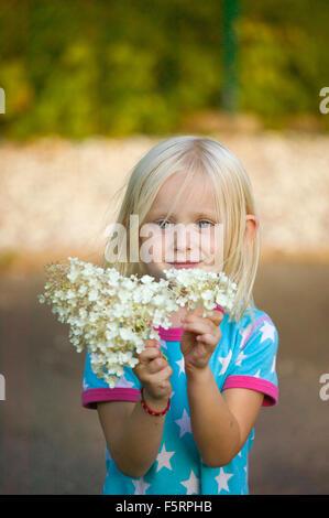 Sweden, Sverige, Narke, Filipshyttan, Portrait of girl (4-5) holding flowers - Stock Photo
