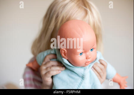 Sweden, Vastergotland, Lerum, Girl (4-5) hiding behind doll - Stock Photo
