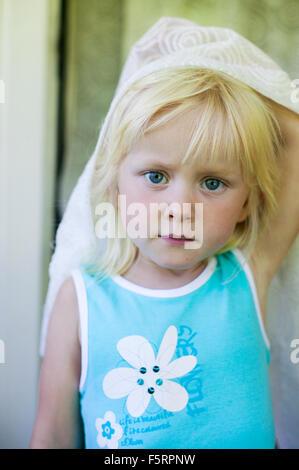 Sweden, Narke, Filipshyttan, Portrait of girl (4-5) holding curtain - Stock Photo