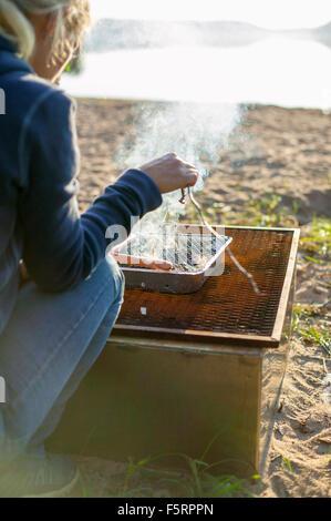 Sweden, Vastergotland, Lerum, Woman cooking by lake - Stock Photo