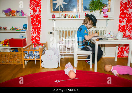 Sweden, Vastergotland, Lerum, Boy (6-7) writing in note pad - Stock Photo