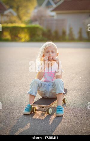 Sweden, Vastergotland, Lerum, Portrait of girl (6-7) on skateboard - Stock Photo