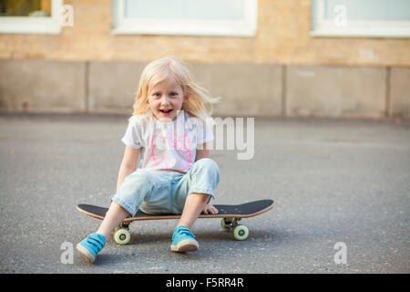 Sweden, Vastergotland, Lerum, Girl (6-7) sitting on skateboard - Stock Photo