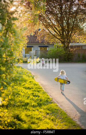 Sweden, Vastergotland, Lerum, Girl (6-7) walking to boy (8-9) with skateboard - Stock Photo