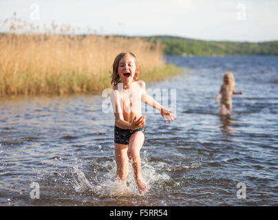 Sweden, Vastergotland, Lerum, Lake Aspen, Boy (8-9) and girl (6-7) playing in lake - Stock Photo
