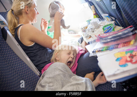 Sweden, Woman with yawning child on plane - Stock Photo