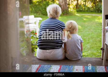 Sweden, Narke, Filipshyttan, Woman sitting with girl (6-7) on porch - Stock Photo