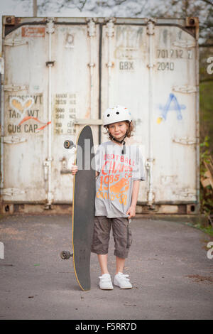 Sweden, Vastergotland, Lerum, Portrait of boy (8-9) with skateboard in front of gate - Stock Photo