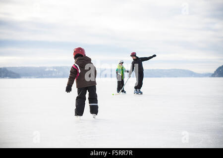 Sweden, Vastergotland, Lerum, Lake Aspen, Mom playing ice hockey with her two children (6-7, 8-9) on lake - Stock Photo